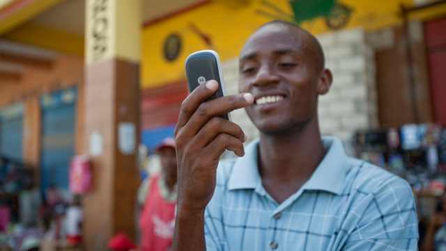 Jean Louis Thomas of Haiti writes a text message to a friend. Many people living on less than $2/day already have access to a mobile phone. (Image courtesy of the Gates Foundation)